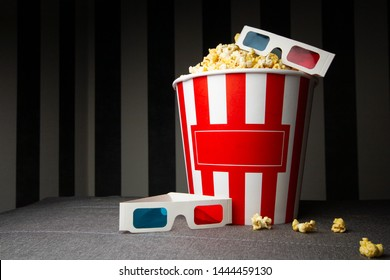 one cardboard buckets of popcorn stand on a gray background with 3D glasses, on the packs there is an copy space for text
