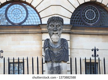 One of the carved heads on a pillar surrounding the perimeter of the Sheldonian Theatre in Oxford England called Emperor Heads but probably philosophers heads each one has a different style of beard