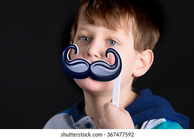 One caucasian boy with mustache prop on black background.
