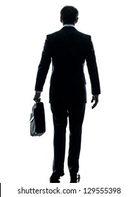 one caucasian businessman walking rear view in silhouette studio isolated on white background