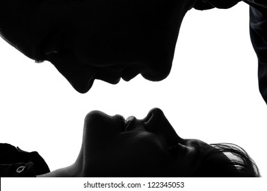 one caucasian couple woman man kissing full length  in silhouette studio isolated on white background