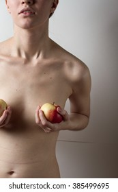 One caucasian girl covers her small Breasts with two red apples on a light background