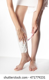 one Caucasian girl shaves legs women's refillable razor with shaving cream on a white background