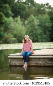 One Caucasian High School Senior Girl Sitting on Dock at Lake Outside Summertime.