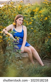 One Caucasian High School Senior Girl in Blue Dress Sitting on Wooden Bench