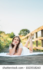 One Caucasian High School Senior Girl Laying Down On Wooden Bridge Walkway
