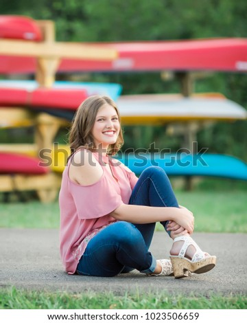 One Caucasian High School Senior Girl wearing cold shoulder top Outside during Summertime. Kayak boats in background.