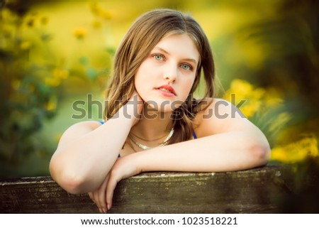 One Caucasian High School Senior Girl Looking Back Over Bench Outside By Yellow Flowers