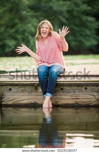 One Caucasian High School Senior Girl Sitting on Dock at Lake Outside Summertime.
