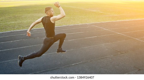 one caucasian male is doing a sprint start. running on the rubber track. Track and field runner in sport uniform. energetic physical activities. outdoor exercise, healthy lifestyle. running jumps.