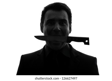 one caucasian man biting knife in silhouette studio isolated on white background