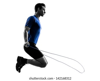 one caucasian man exercising jumping rope in silhouette studio  on white background