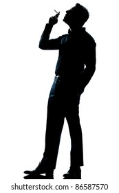 one caucasian man smoking cigarette full length silhouette in studio isolated white background
