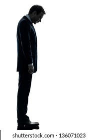 one caucasian sad business man  looking down  in silhouette studio isolated on white background