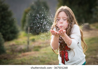 One caucasian seven year old girl blows glitter outside eyes shut