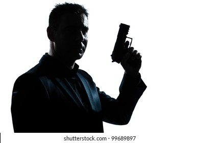 one caucasian spy criminal policeman detective man holding gun portrait silhouette in studio isolated white background