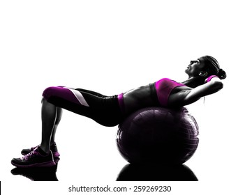 one caucasian woman exercising  fitness ball crunches  in studio silhouette isolated on white background