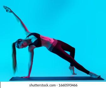 une femme caucasienne exerçant des exercices de yoga en studio silhouette isolée sur fond bleu