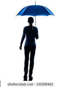 one caucasian woman rear view walking  holding umbrella  in silhouette studio isolated on white background