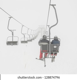One of chair lifts in a ski resort of a valley of Zillertal in the fog - Mayrhofen region, Austria