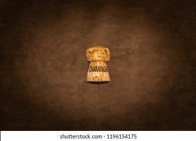 One champagne cork with text against brown suede texture seen from above.