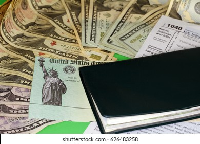 One checkbook on a 1040 tax form, a tax refund check and a variety of cash paper money. A tax refund check with paper money, a checkbook and a 1040 tax form.