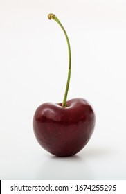 One cherry with stem isolated on white background. Vertical portrait of the healthy, mellow dark red fruit. Proper food for vegan, vegetarian.