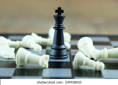 One chess with black king standing and outstanding among the collapse of fall in line, business concept able to survive or dominant from destruction. Selective focus on board.