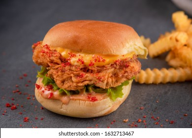one chicken slider consist of chicken breaded breasts and cheddar cheese, mixed sauce and lettuce and mashed Cheetos and fries