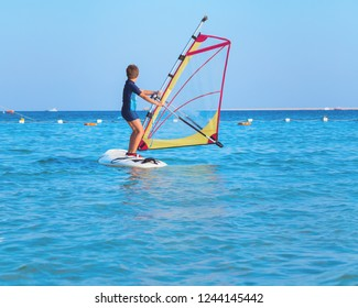 One child learning to windsurf in the sea at beautiful sunset light, close up, windsurfing passtime and school with copy space