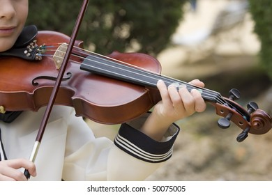 one children playing the violin in a beautiful park