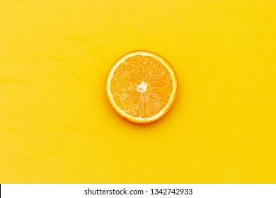 One circle slice of fresh ripe orange with pulp and peel on yellow and pink background. Top view. Clipping path - image.