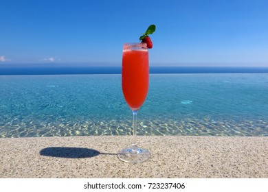 one cocktail in champagne glass by pool single vacation solo holiday concept