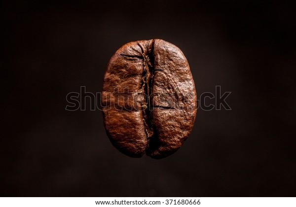 One coffee bean dark espresso on a black background.