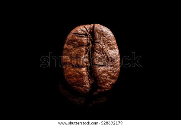 One coffee bean isolated on pure black background. Big macro grain coffee black espresso. Dark roasted coffee.