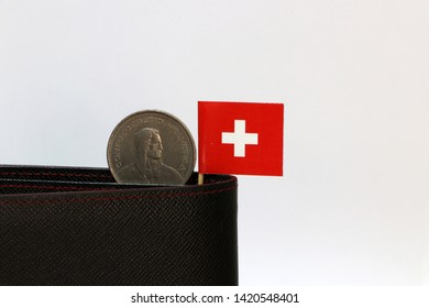One coin of five swiss Franc and mini Switzerland flag stick on the black wallet with white background. Franc Schweiz money, the concept of finance.