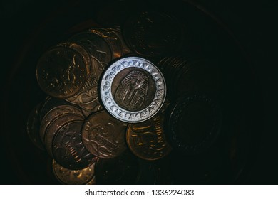 one coin with the image of the Egyptian pharaoh lies among other coins in the dark lit by a ray of light