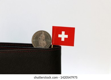 One coin of one swiss Franc and mini Switzerland flag stick on the black wallet with white background. Franc Schweiz money, the concept of finance.