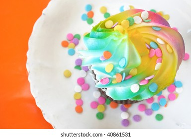 One colorful cupcake with sprinkles all sitting on a white plate.