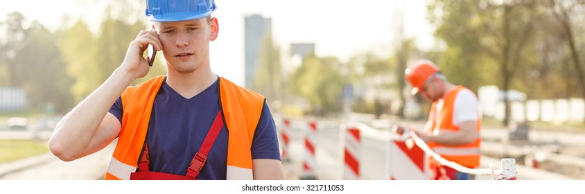 One of the construction workers is calling