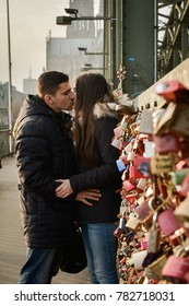 One couple kissing on a bridge in Cologne, full of love locks