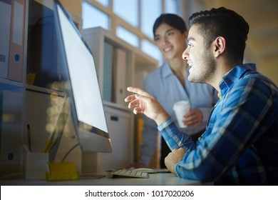 One of creative designers sitting in front of computer monitor and showing curious design project to colleague while discussing it with her