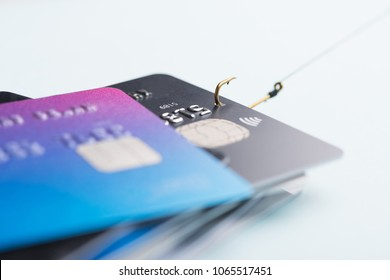 One credit card being stolen by fishing hook from pile of other bank cards, fraud data leak money stealing phishing concept