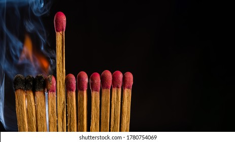 one in the crowd concept of matchstick with flames, with the idea of distance, prominence, dedication and humility, copy space
