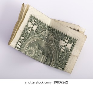 one crumpled one dollar banknote, isolated on white background.