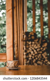 One cup on a wooden table. In the background, stacked firewood. Blurred background. Closeup