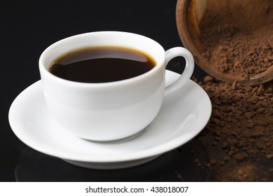 one cup, white cup, black background
