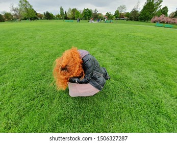 One Curly Ginger Young Woman Bending Down in the Middle of a Green Grass Field, Concept of Loneliness, Solitude and Seclusion