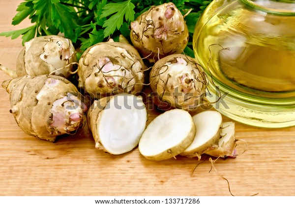 One cut and a few whole tubers of Jerusalem artichoke, parsley and a bottle of vegetable oil on a wooden board