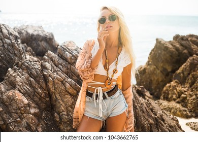 one cute beautiful girl in a Boho style dressed shirts shorts light cape bracelets necklaces, in the hair decorative feathers colored, standing in a sensual pose against the background of the rocks